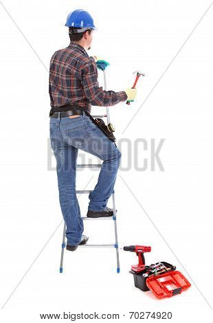 Carpenter With Hammer On The Stepladder