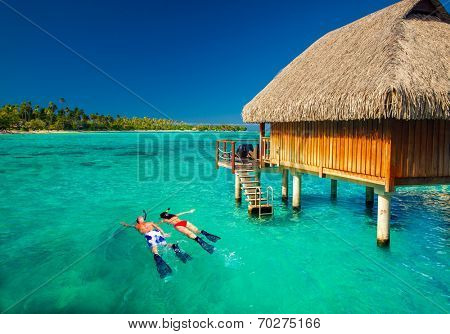 Young couple snorkeling from hut over blue tropical lagoon
