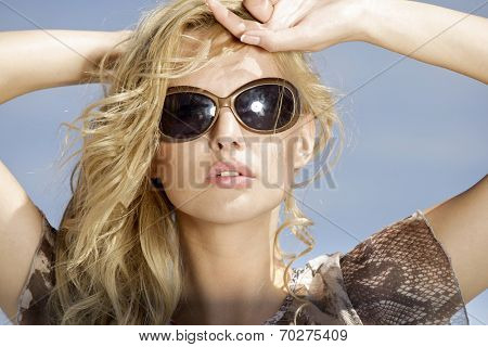 portrait of beautiful young adult blonde girl in sunglasses on background blue sky
