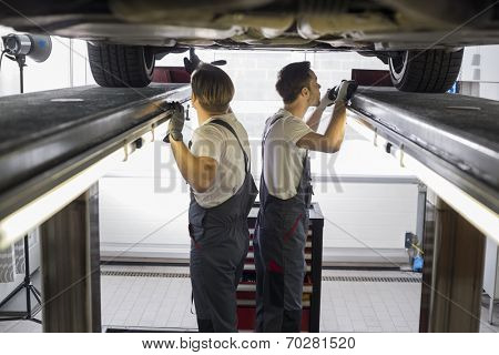 Side view of maintenance engineers examining car in repair shop