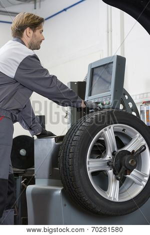 Side view of mid adult male mechanic repairing car's wheel in workshop