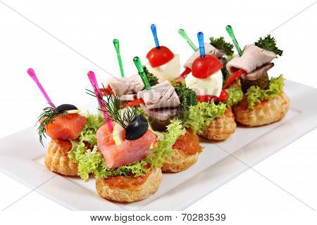 Assorted Canapes-sandwiches On Plate Over White Background
