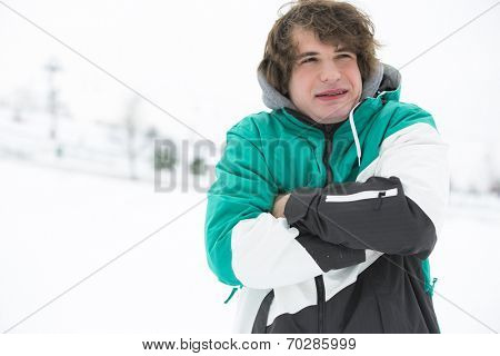 Young man in jacket shivering in snow