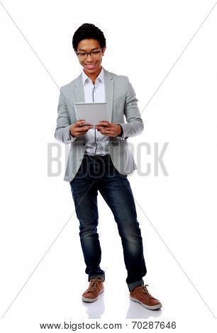 Full length portrait of a happy asian man using tablet computer over white background