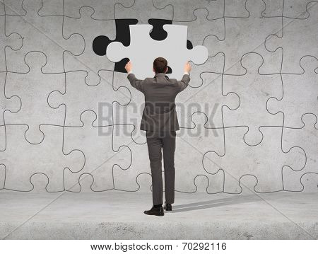 business, development and people concept - businessman in suit setting piece of puzzle to the wall background