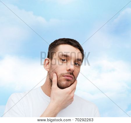 health and beauty concept - beautiful calm man touching his face