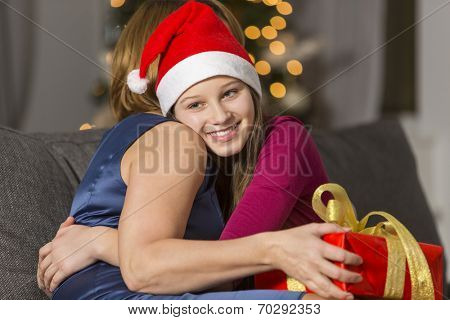 Happy girl hugging mother during Christmas at home