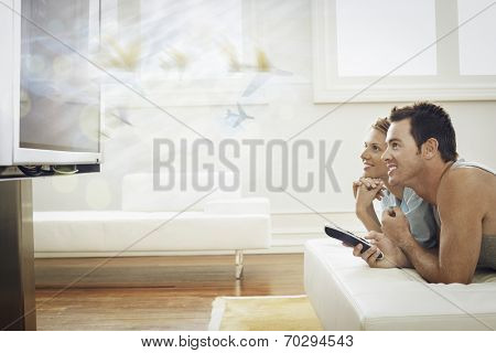 Side view of happy young couple watching plasma TV at home