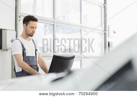 Young male automobile mechanic using computer in repair shop