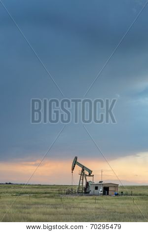 oil rug (pumpjack) against stormy sunset sky in Pawnee National Grassland near Grover, Colorado