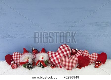 Blue Wooden Christmas Background With Brownie And Red Checked Hearts.