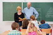 image of senior class  - Teacher with his young attractive female teaching assistant standing in front of a class of small girls and boys as they discuss something from a textbook - JPG