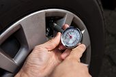 image of air pressure gauge  - Cropped image of mechanic checking tire pressure using gauge - JPG