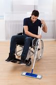 stock photo of handicap  - Full length of young handicapped man mopping hardwood floor while sitting on wheelchair in house - JPG
