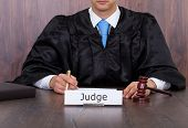 stock photo of courtroom  - Midsection of judge with mallet sitting at desk in courtroom - JPG