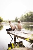 foto of dock a pond  - two boy playing at the lake sitting on a wooden dock looking at the water - JPG