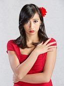 stock photo of sulky  - Beautiful young Asian woman with red flower in hair - JPG