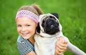 stock photo of pug  - Little girl and her pug dog on green grass - JPG