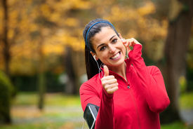 stock photo of gesture  - Successful female athlete doing positive thumbs up gesture and wearing earphones before running or exercising outdoor in autumn - JPG
