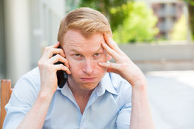 stock photo of annoying  - Closeup portrait young man annoyed frustrated pissed off by someone talking on his mobile phone bad news isolated outdoors outside background - JPG