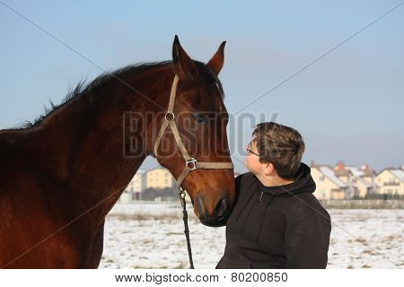 Teenager Boy And Bay Horse Portrait In Winter