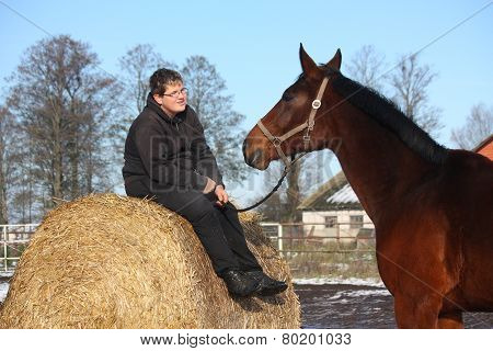 Teenager Boy Resting On The Hay Bale And Bay Horse