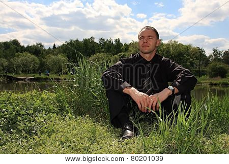 Tired businessman on nature.