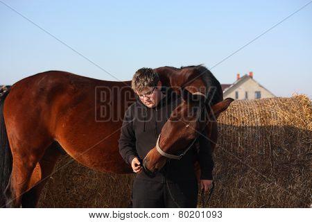 Teenager Boy In Black Hugging Brown Horse
