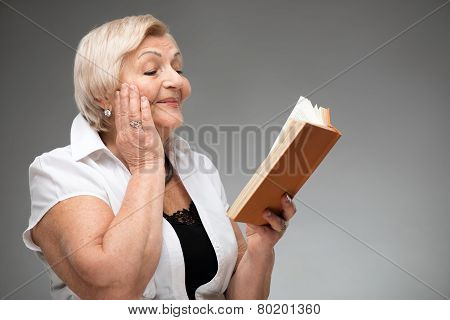 Elderly woman holding yellow book