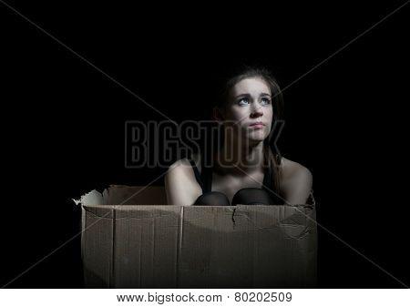 Upset girl posing sitting in cardboard box
