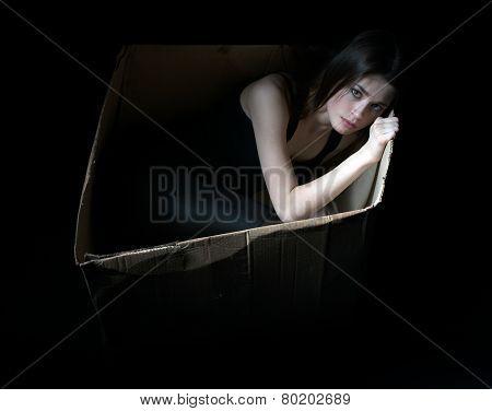 Concept of homeless. Upset girl in cardboard box