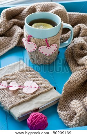 A Cup Of Tea In Sweater, Old Notebook With Hearts Of Felt, Beige Knitted Blanket And Spokes