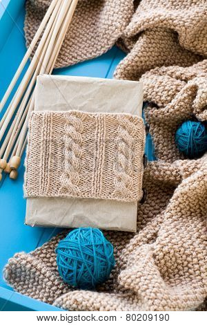 Old Notebook With Knitted Wrap, Beige Knitted Blanket And Spokes Lie On Blue Background