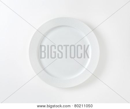 white plate with fluted rim on white background