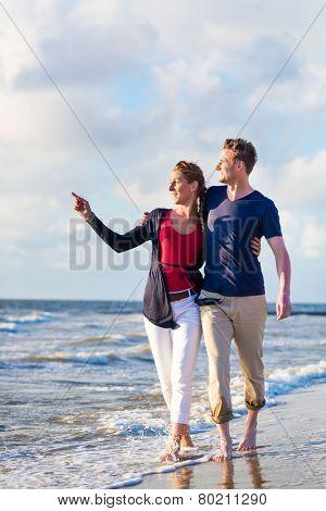 Couple take a romantic walk through sand and waves at German north sea beach
