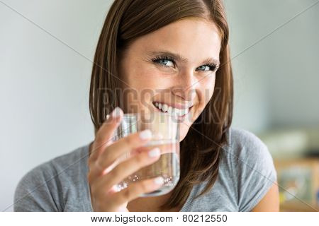 Portraiture of young smiling woman with glass of water