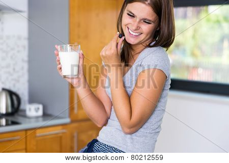 Smiling housewife relaxing in kitchen_