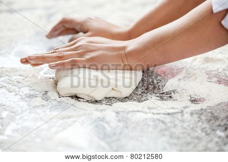 Cropped image of female chef's hands kneading dough at messy counter in commercial kitchen