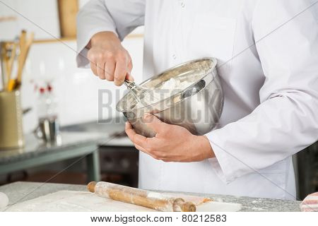 Midsection of male chef mixing batter with wire whisk in bowl at commercial kitchen counter