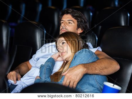 Loving mid adult couple watching movie in cinema theater