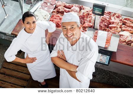 High angle portrait of confident male and female butchers standing at butchery counter