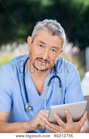 Portrait of male nurse using digital tablet at nursing home