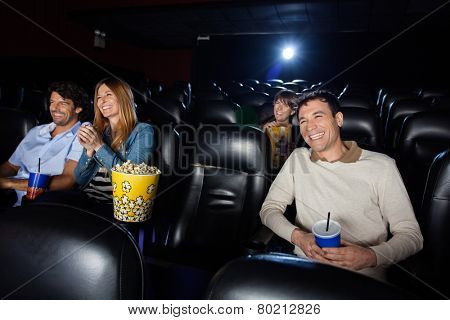 Happy people watching film in movie theater