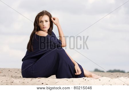Young adult sexy attractive and sensuality brunette woman posing in violet dress.
