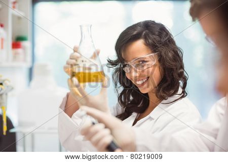 Pretty science student smiling and holding beaker at the university