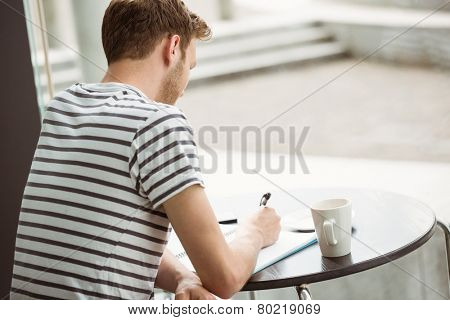 Student sitting with a hot drink and writing on notepad in cafe at the university