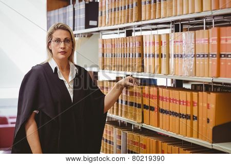 Portrait of a serious lawyer with reading glasses in library