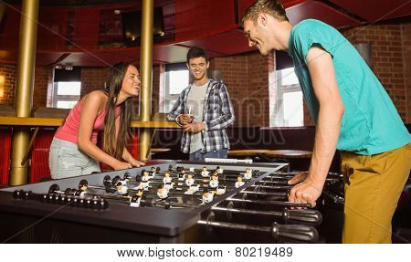 Smiling friends student playing table football in competition in a pub