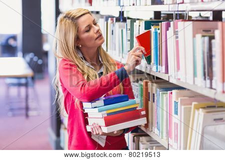 Mature student in library picking book at the university