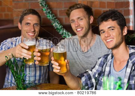 Happy friends toasting with pints of beer on patricks day in a bar